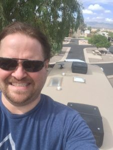 A white man with brown hair and a short beard wearing sunglasses and a blue shirt is looking at the camera, with an RV roof behind him and the view of an RV park in the distance.