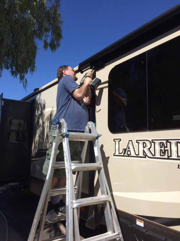A man satnding on a ladder next to an RV, using a drill to work on the slide-out.