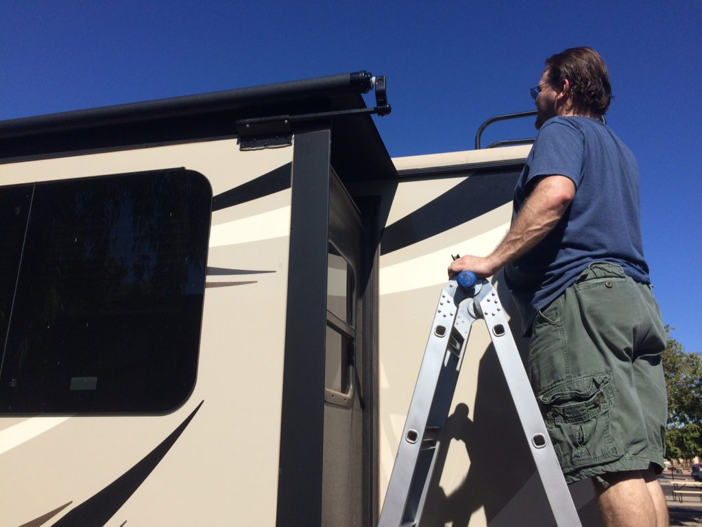 A man standing on a ladder next to an RV slide-out. He is wearing a blue shirt, green shorts, and sunglasses.