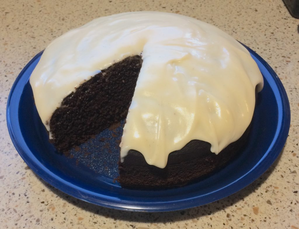 A dark cake with light icing on a plate.