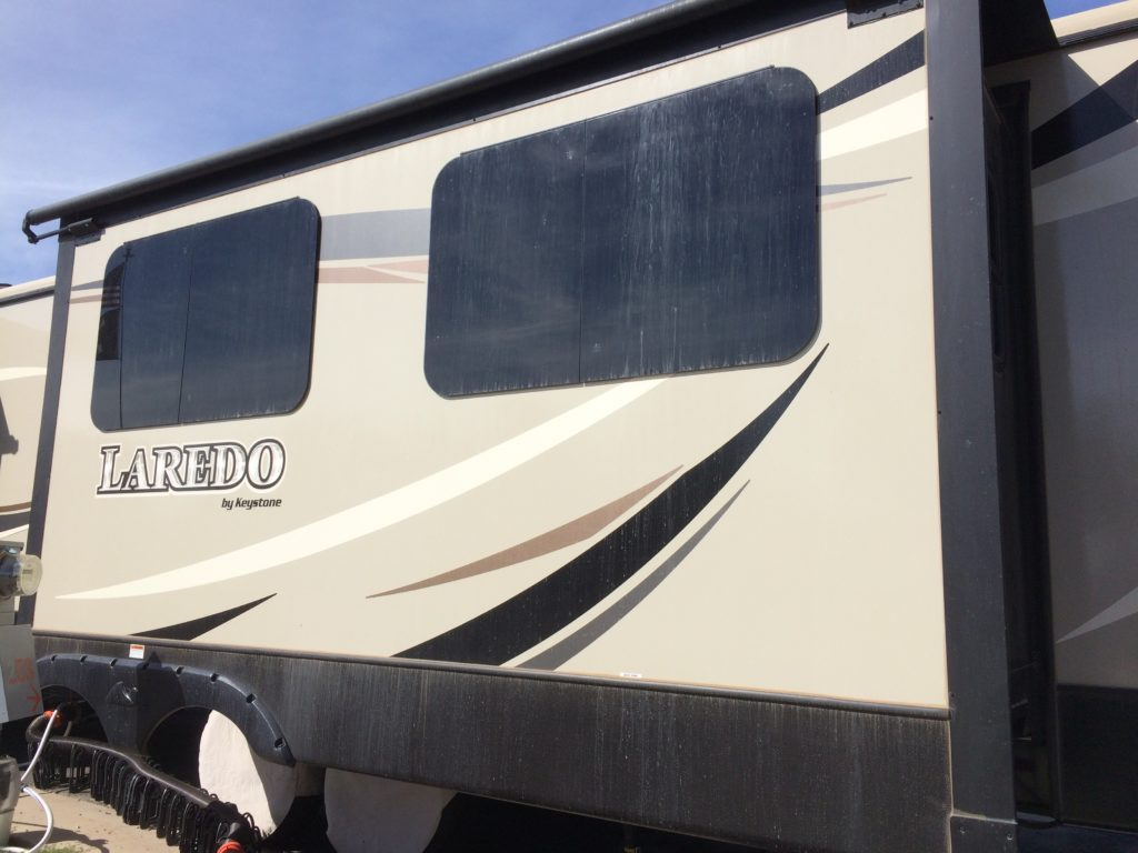 The side of an RV, streaked with dust.