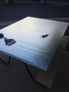 A piece of mylar-covered foamboard on a table, with a broom and dustpan.