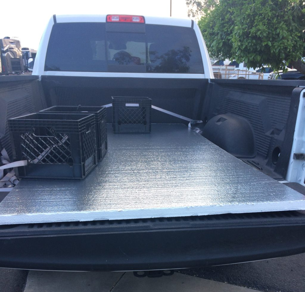 An open truck bed, with a piece of foam board strapped in. some milk crates sit on top of the board.