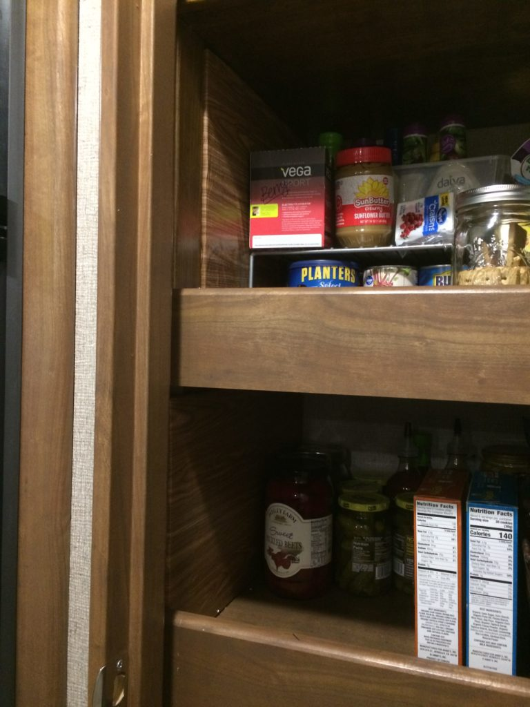 Two shelves of a pantry, with the food pushed aside so the insulated walls can be seen. There are several jars of pickles in the pantry.