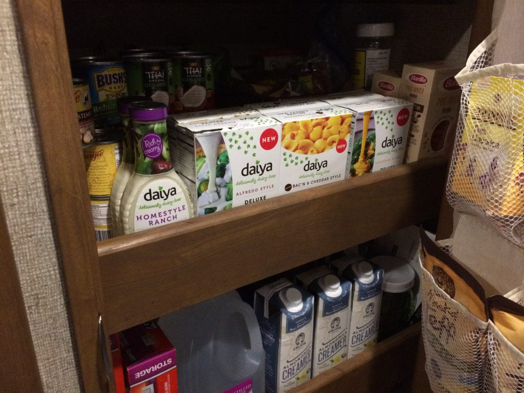 Pantry shelves with multiple containers of Daiya cheese, Daiya salad dressing, and Califia Farms coffee creamer.