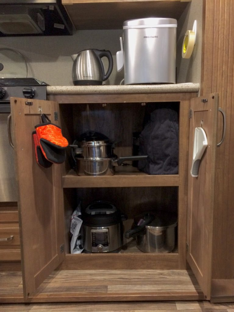 an open cabinet containing an Instant Pot, stovetop pressure cooker, two sauce pans, and a covered mixer. The counter above the cabinet has an electric tea kettle and an ice maker. Hanging from each open cupboard door is a pair of oven mitts and a jar opening device.
