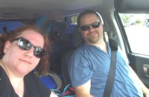 A white man and white woman in the front seat of a vehicle, wearing seatbelts and smiling at the camera.