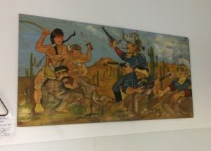 A painting of three native american men in traditional garb, holding spears and bows, facing three white men in military uniforms pointing guns at them.