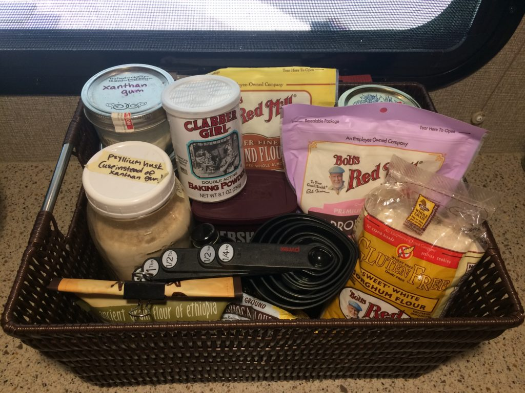 A basket of gluten-free flours and baking ingredients, with a set of measuring spoons and cups on top.
