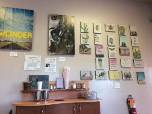 A wall of art for sale behind a coffee sugar and creamer station.