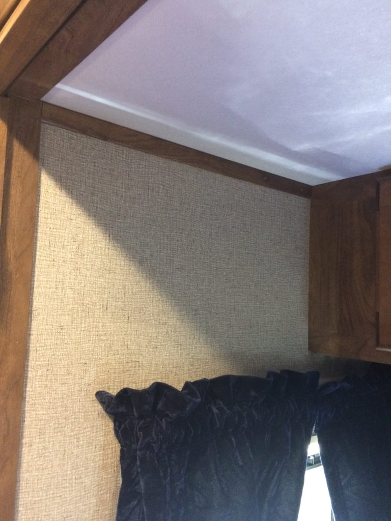 view of the wall space above the left bedside window