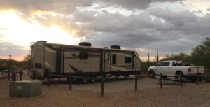 A white pickup truck parked in front of an RV trailer, with the sun setting and clouds in the distance.
