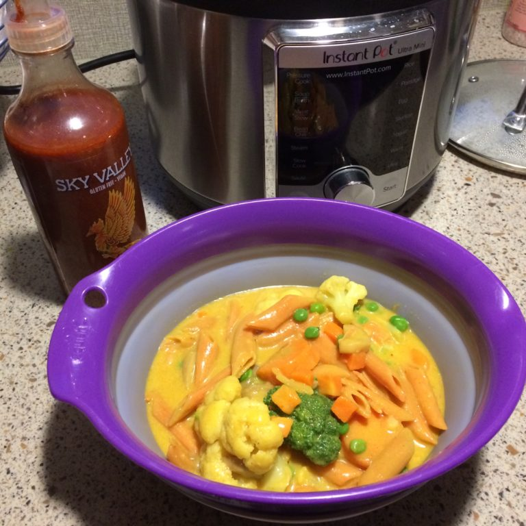 A bowl of curried pasta with sriracha and an instant pot in the background.