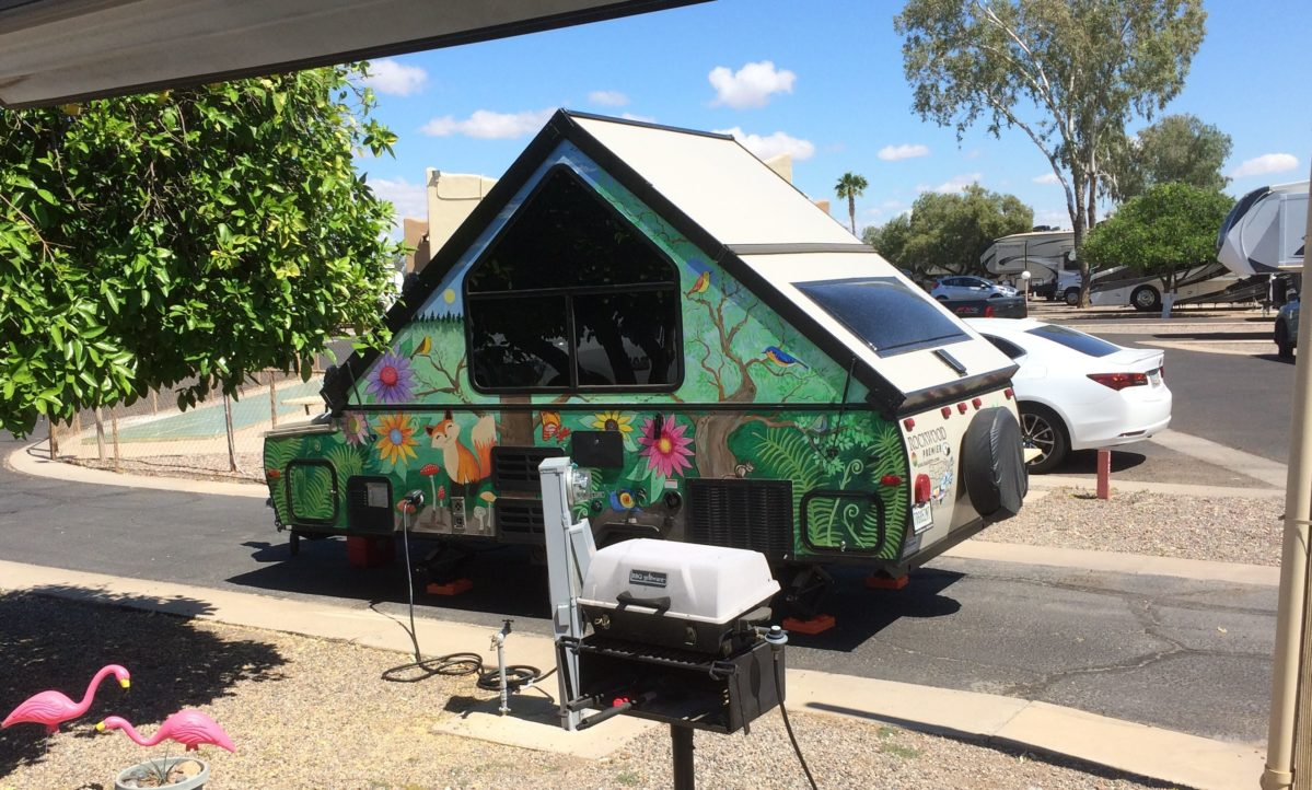 An A-frame camper hand painted green with lots of flowers and wildlife.