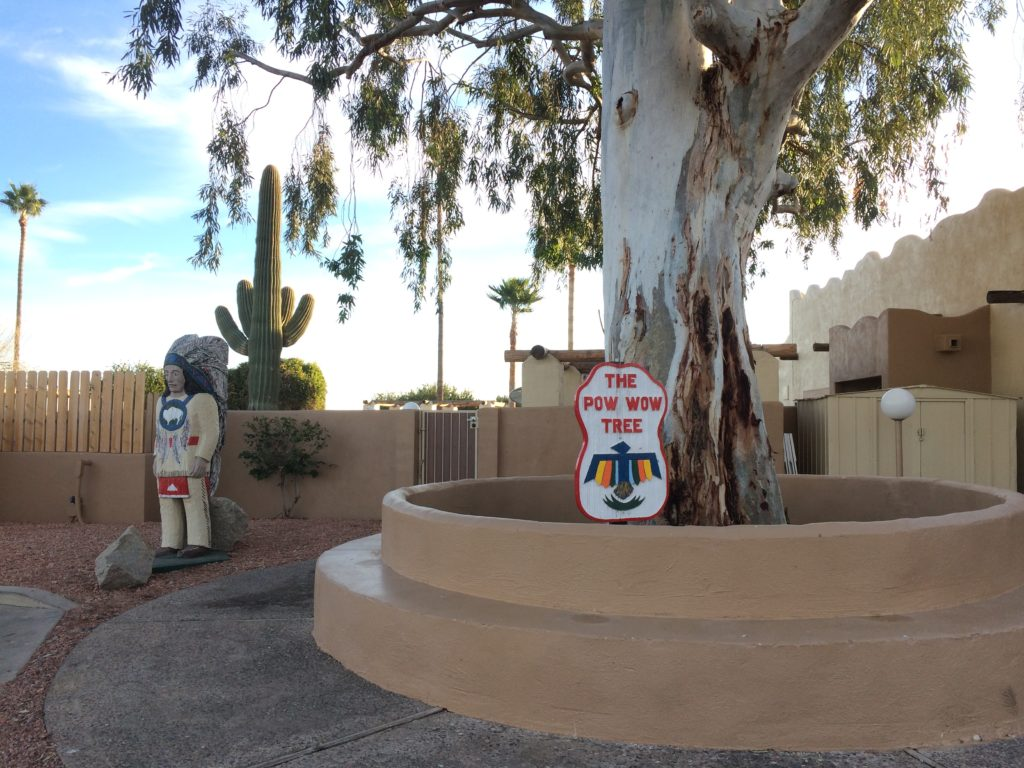 """a wooden indian statue next to a very large tree with a sign in front of the tree that says """"the pow-wow tree."""""""