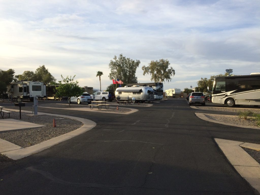 An RV park with wide roads and some occupied and empty spaces.