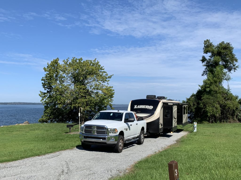 A truck parked in front of an RV, with two trees on each side, with grassy ground, blue skies, and water in the distance.