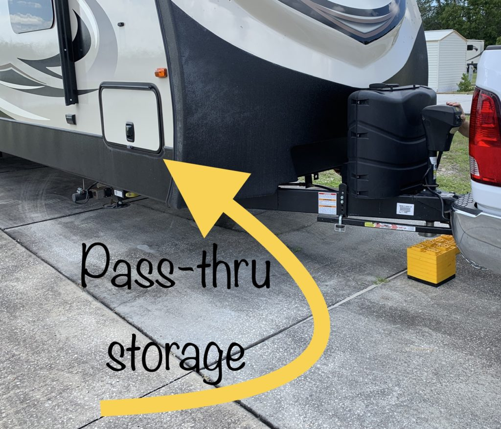 "the front of an RV with an arrow pointing to the storage door on the bottom side, and the words ""pass-thru storage."""