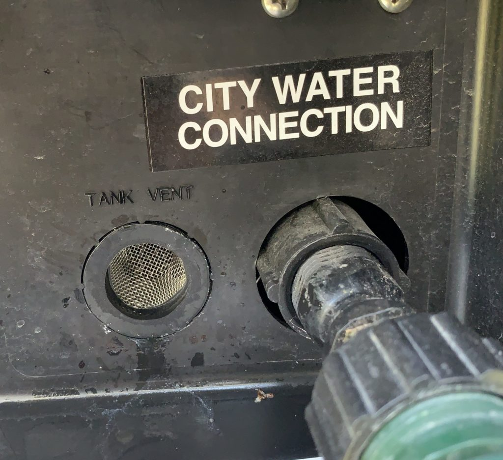 Close up view of the fresh water inlet connection and the fresh water tank vent