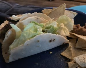tacos with lettuce bursting out the top, and chips on the side.