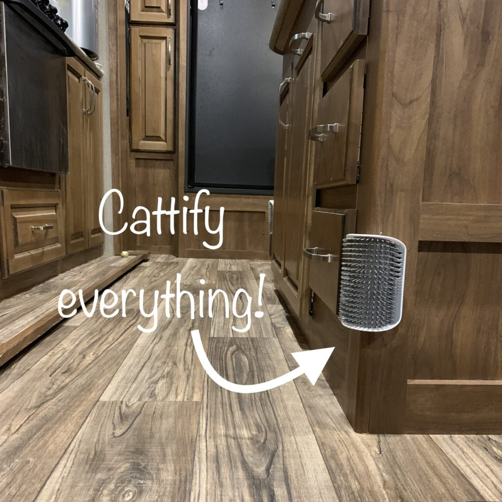 a brustly cat rubbing surface mounted to the corner of a kitchen island in an RV. the stove and fridge are in the background.