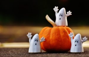 three ghost toys around a small orange gourd.