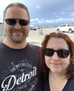 a man and a woman wearing sunglasses and smiling at the camera. a beach is behind them.