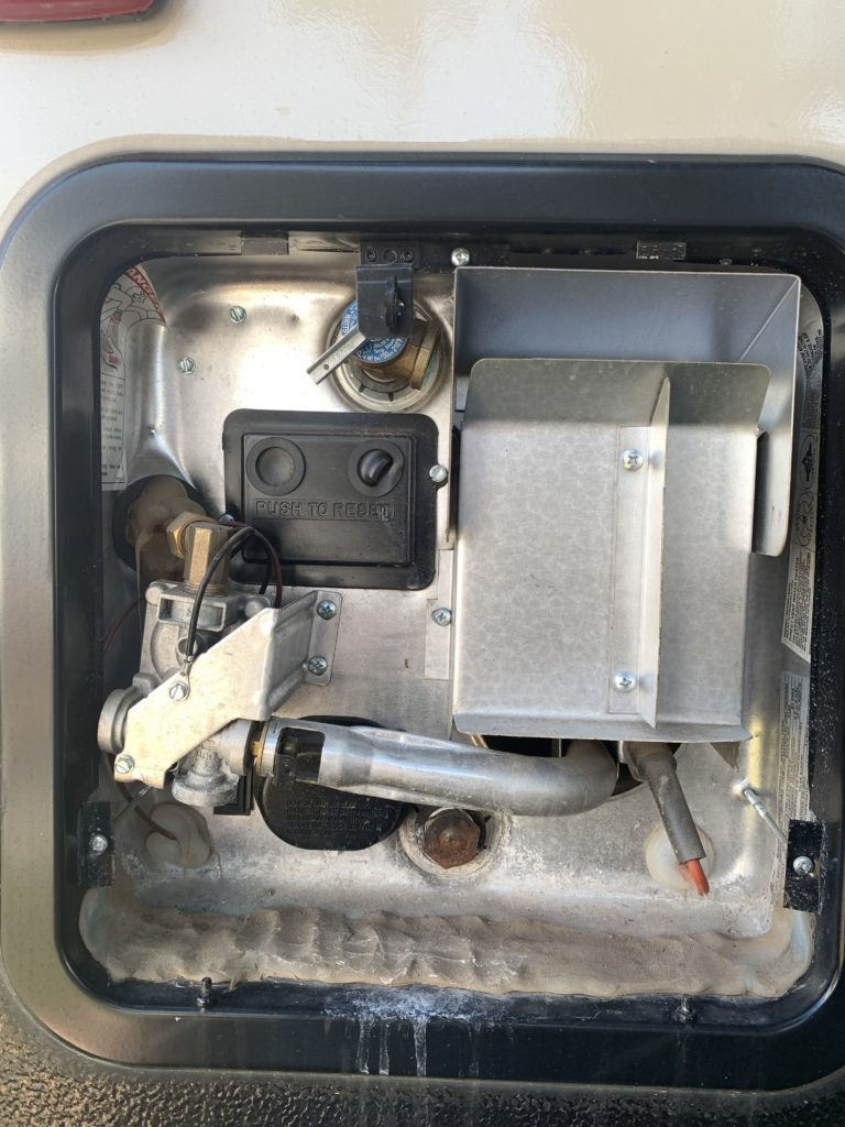 View of the RV water heater with the cover open