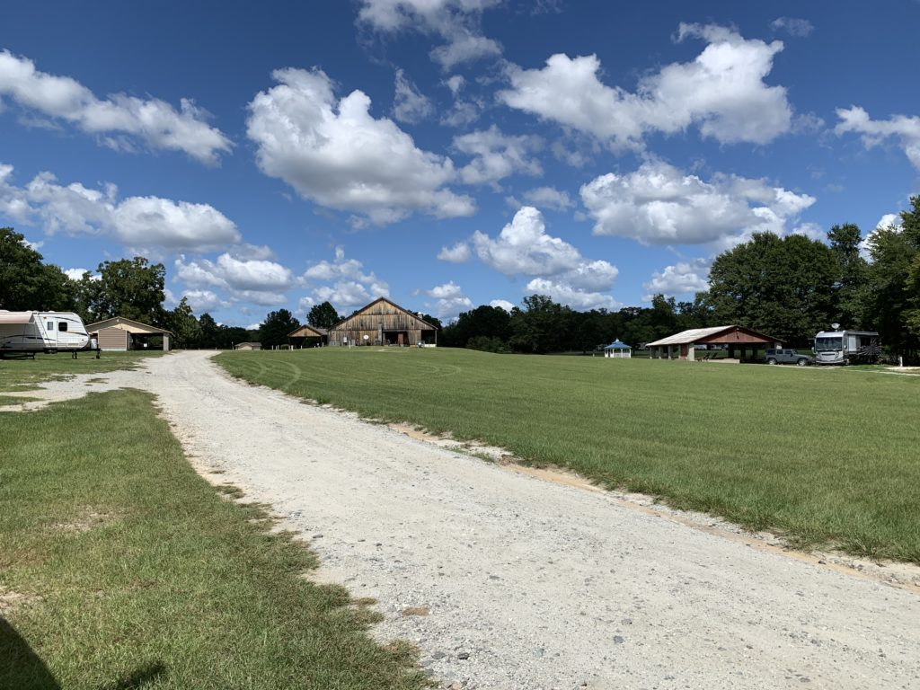 a grassy field and gravel road under blue skies with big puffy clouds.