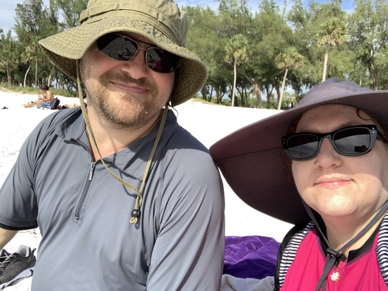 a light skinned man and a light skinned woman smiling at the camera, wearing big floppy beach hats and sunglasses.