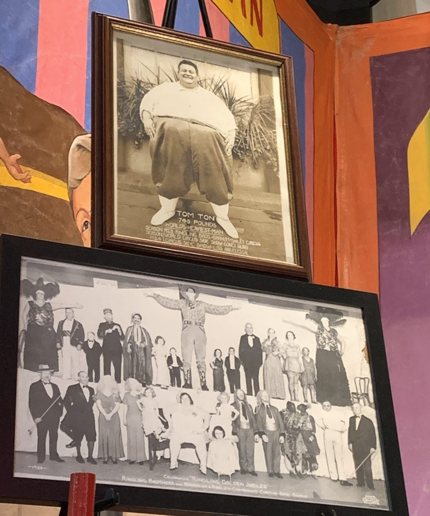 Fatman Tom Ton pictured over another picture of a large group of sideshow performers.