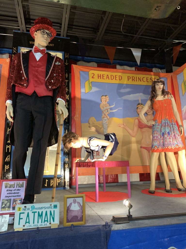Wax figures of a 4-legged woman, a woman with no legs, and Ward Hall, on a stage behind a display with a photo of a very fat man and the new hampshire license plate FATMAN.