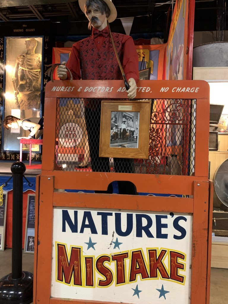 "a sideshow booth advertising ""nature's mistake"" with free admission for doctors and nurses."