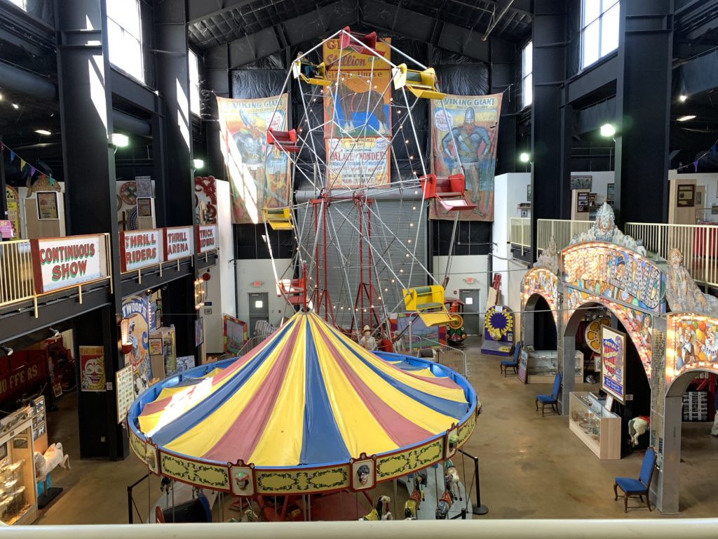 The view of the museum from the second floor, with a large carousel and ferris wheel, and many displays.