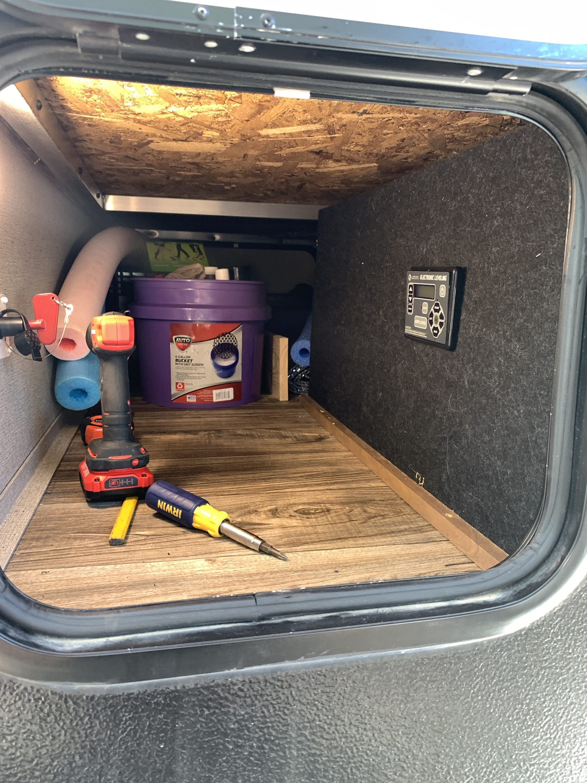 view of the nose pass through storage area. in view are a bucket, some tools, and various pool noodles. There is a carpeted false wall on the right hand side with our automatic leveling system control attached.