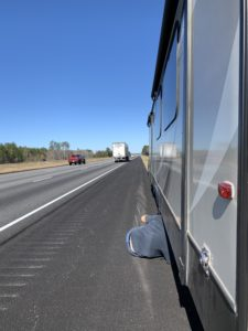 an RV on the side of the highway, with a person mostly underneath the RV and only their back showing.