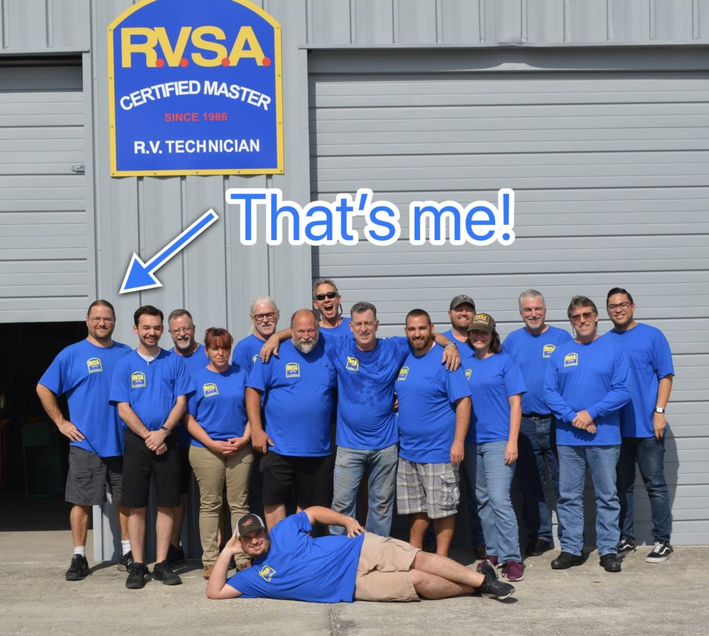 a group of adults wearing matching blue shirts under an RV Service Academy sign. An arrow points to one light skinned man with his hands on his hips and smiling, with the words Thats me!