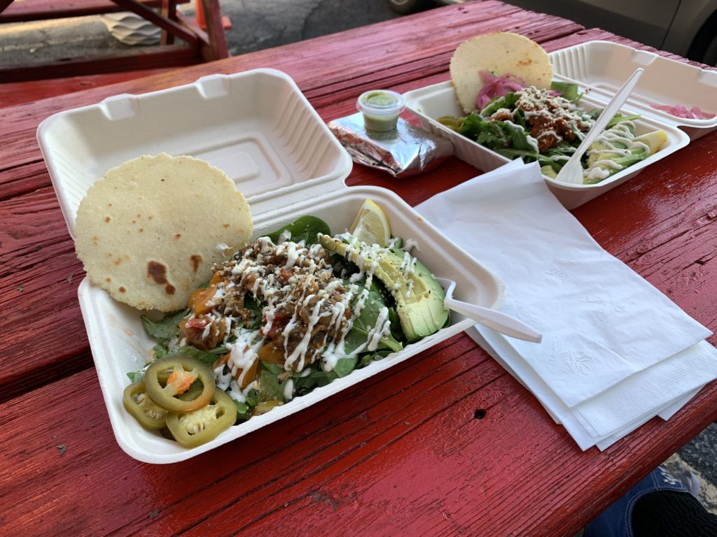 Two clamshell takeout containers filled with delicious food, and tortillas on the side.