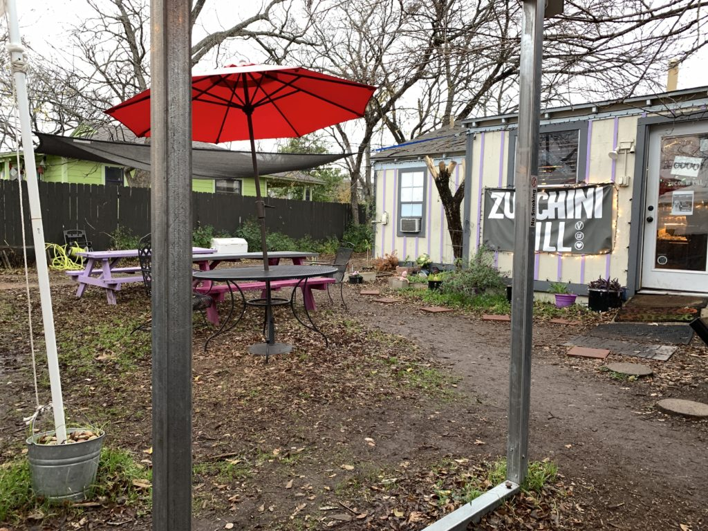 The view from a covered seating area, with metal poles in the way. Zucchini Kill can be seen in the background, and a picnic table has a big red umbrella sheltering it.
