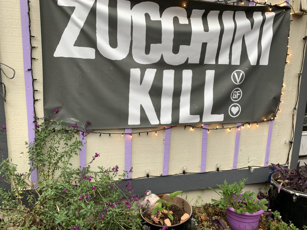 A banner for Zucchini Kill bakery, with Gluten free and vegan symbols. a container garden beneath the banner has green plants and doll parts.