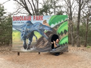 a dinosaur park photo op with a space for a person to stand under a dino mouth, the person is faking a scared expression.