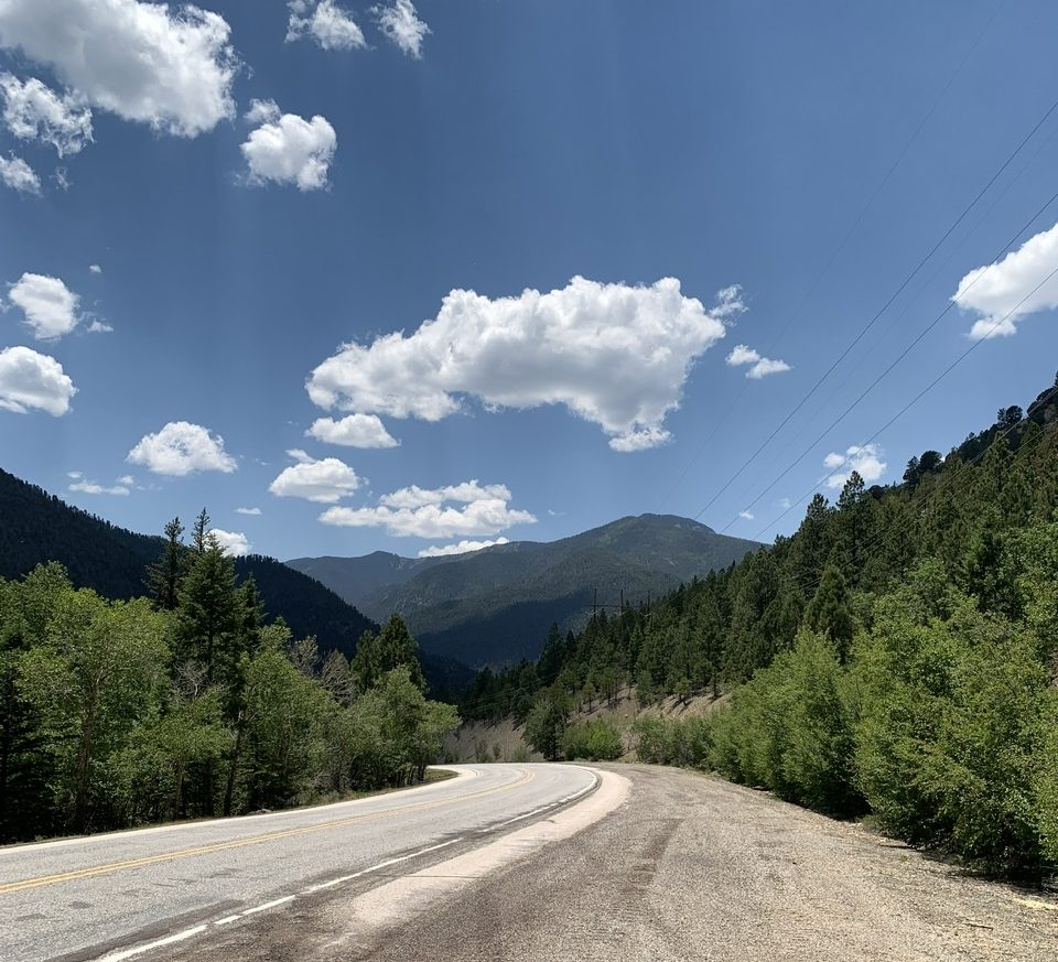 photo of the road curving off into the distance, with trees on either side, mountain in the distance, and blue skies with just a few clouds.