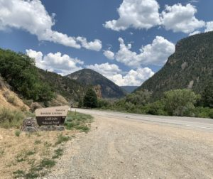 Photo of the sign for the Questa Ranger Station with mountains in the distance, blue skies, and big puffy clouds.