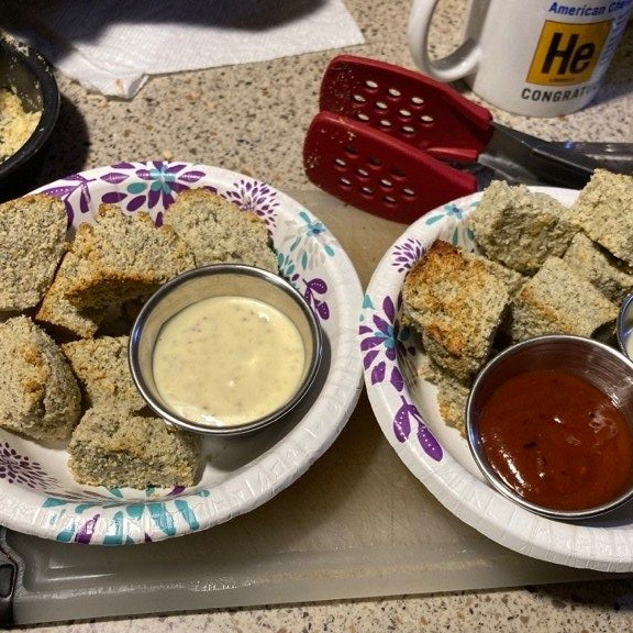 Rough looking cubes of tofu with browned edges and cups of dip