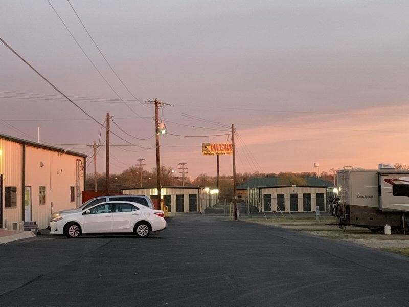 photo across a parking lot and of the sky at dusk, with storage units in the far distance and a building to the left. RV spaces are on the right.