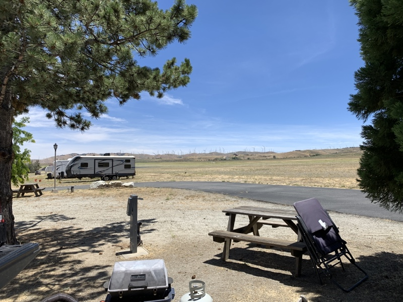 Photo of a picnic table in the foreground, an Rv in the distance, and mountains beyond that.