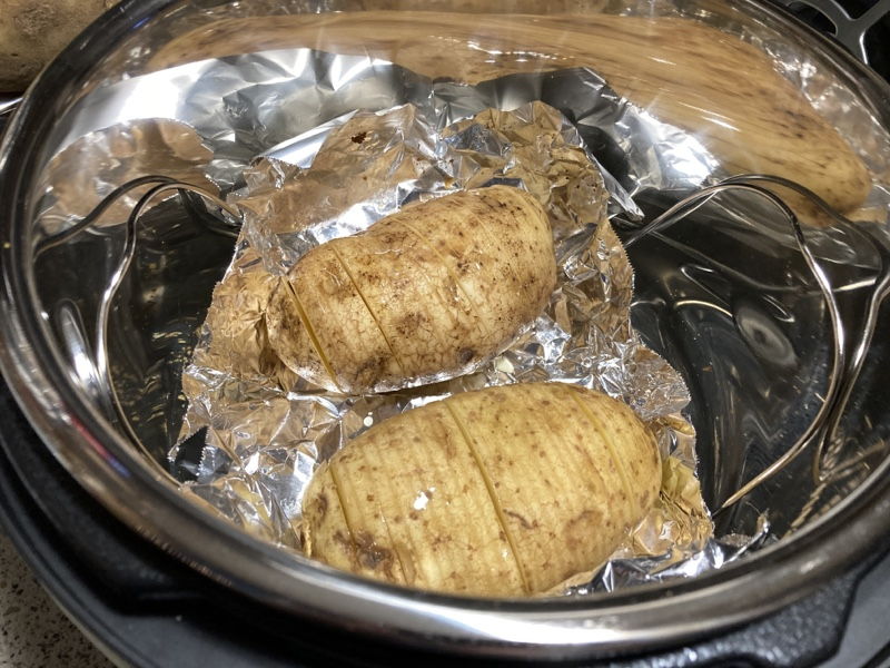 Two raw potatoes with very thin vertically cut slices on a piece of foil in a pot