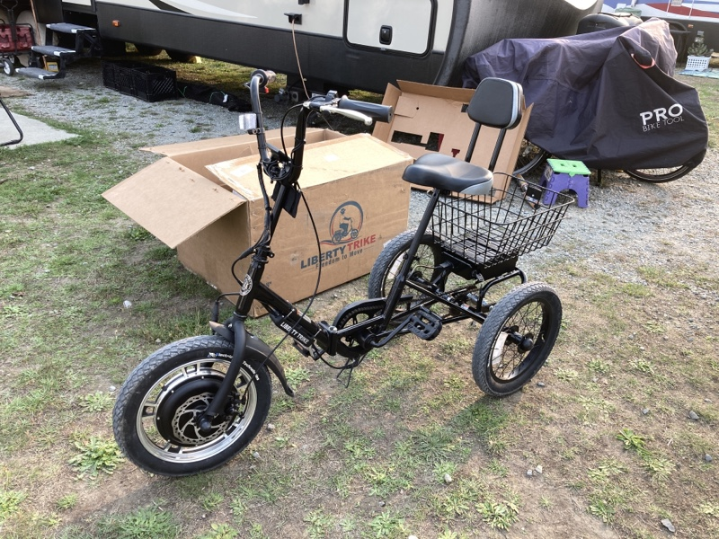 A black tricycle in front of a liberty trike box