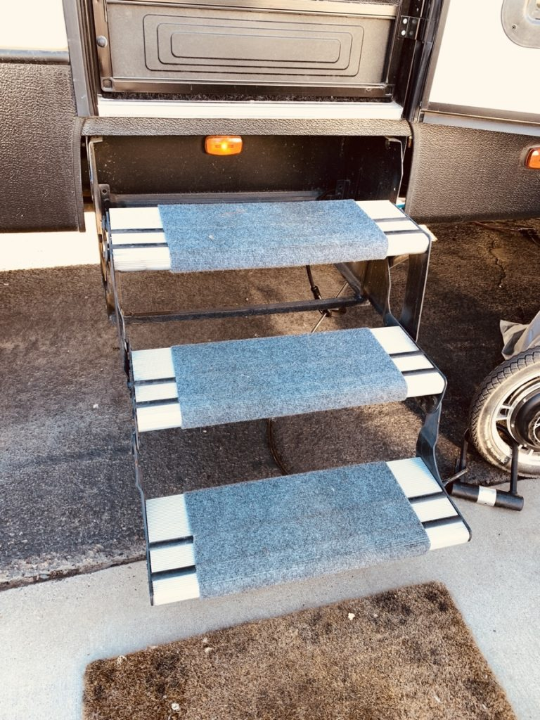 Three RV steps with blue carpet, and a welcome mat on the ground.