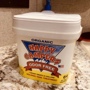 a large tub of Happy Campers holding tank treatment on a bathroom counter.